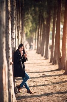 Szczęśliwa i stylowa kobieta hipster biorąc zdjęcie z aparatu fotograficznego na tle sosny