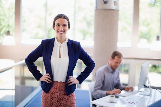 Szczęśliwa i ufna bizneswoman pozycja z rękami na biodrze