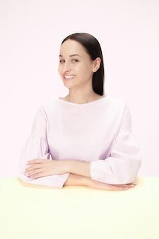 Szczęśliwa i uśmiechnięta biznesowa kobieta siedzi przy stole na różowej przestrzeni