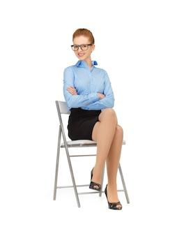 Szczęśliwa i uśmiechnięta kobieta na krześle w okularach