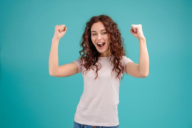 Szczęśliwa i uśmiechnięta kobieta pokazuje zwycięstwo gesty odizolowywających nad turkusowym tłem
