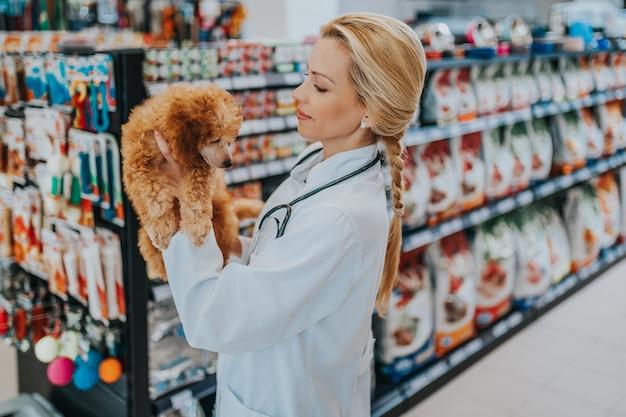 Szczęśliwa i uśmiechnięta kobieta weterynarz w średnim wieku stoi w sklepie zoologicznym i trzyma ładny miniaturowy czerwony pudel.