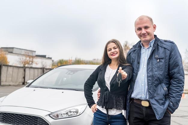 Szczęśliwa i uśmiechnięta para pozuje w pobliżu nowego samochodu