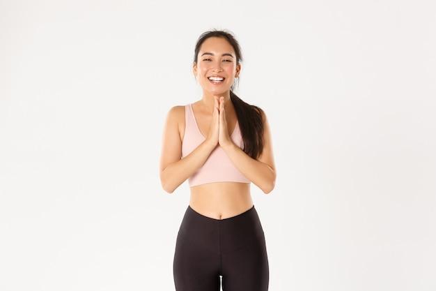 Szczęśliwa i wdzięczna azjatycka atletka dziękuje instruktorowi fitness lub trenerowi za świetny trening treningowy, zaciska ręce, brawa i śmieje się.