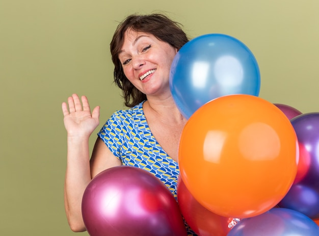 Szczęśliwa i wesoła kobieta w średnim wieku kilka kolorowych balonów macha ręką uśmiechniętą