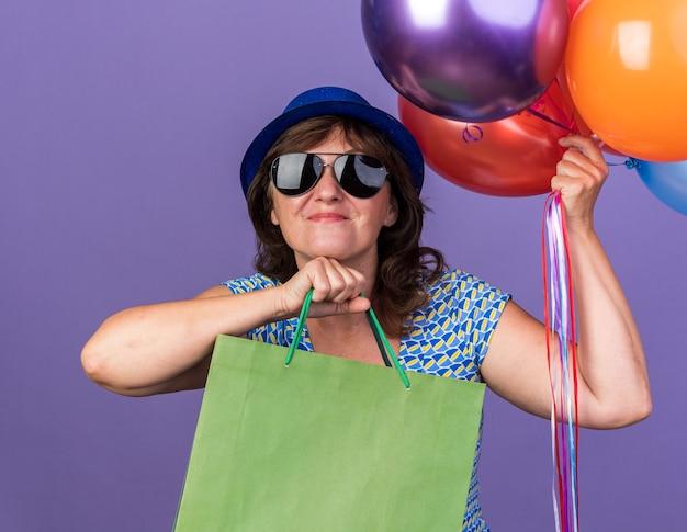 Szczęśliwa i wesoła kobieta w średnim wieku w imprezowym kapeluszu i okularach trzymająca pęk kolorowych balonów i papierowych torebek z prezentami świętująca urodziny stojąca nad fioletową ścianą