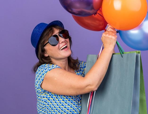 Szczęśliwa i wesoła kobieta w średnim wieku w imprezowym kapeluszu i okularach trzymająca pęk kolorowych balonów i papierowych torebek z prezentami uśmiechnięta świętująca urodziny stojąca nad fioletową ścianą
