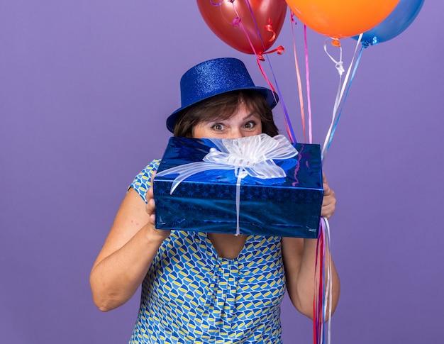 Szczęśliwa i wesoła kobieta w średnim wieku w imprezowym kapeluszu trzymająca pęk kolorowych balonów i prezentująca się zaintrygowana