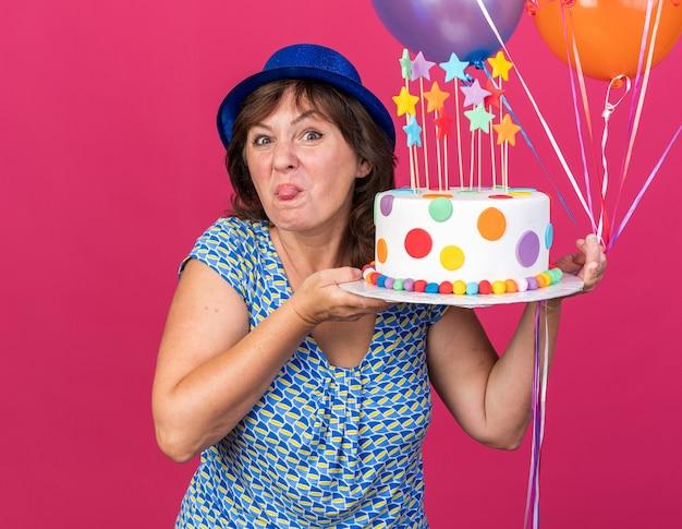 Szczęśliwa i wesoła kobieta w średnim wieku w imprezowym kapeluszu z kolorowymi balonami trzymająca tort urodzinowy bawiąca się z wystawionym językiem
