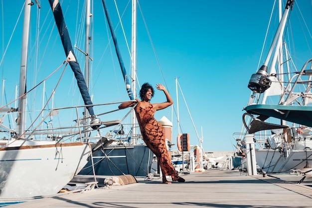 Szczęśliwa i wesoła młoda czarna kobieta mówi ahllo stojąca na pomoście z mnóstwem łodzi dookoła