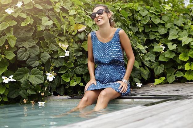 Szczęśliwa i wesoła przyszła mama ubrana w niebieską letnią sukienkę i modne okulary przeciwsłoneczne odpoczywając na basenie z nogami pod wodą