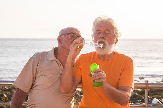 Szczęśliwa i zabawna para seniorów w przyjaźni bawi się bańką mydlaną jak dziecko - bawi się i śmieje