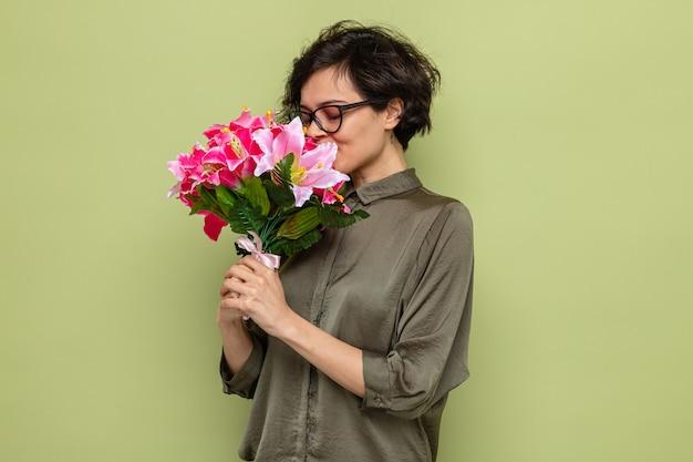 Szczęśliwa i zadowolona kobieta z krótkimi włosami trzymająca bukiet kwiatów i pachnąca