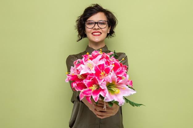 Szczęśliwa i zadowolona kobieta z krótkimi włosami trzymająca bukiet kwiatów patrząca w kamerę uśmiechnięta radośnie świętująca międzynarodowy dzień kobiet 8 marca stojąc na zielonym tle