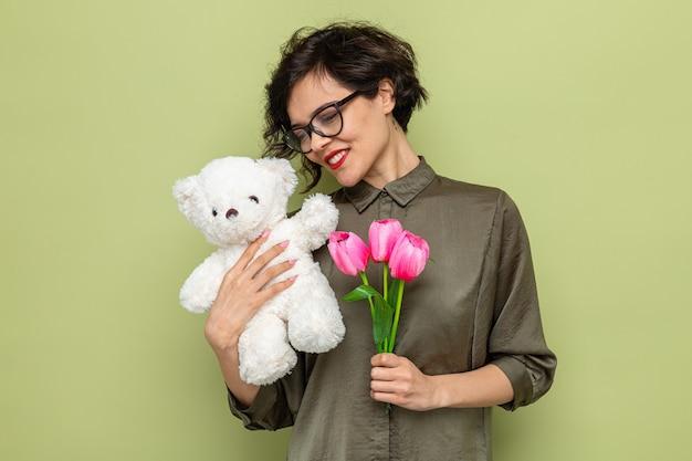 Szczęśliwa i zadowolona kobieta z krótkimi włosami trzymająca bukiet tulipanów i pluszowego misia uśmiecha się radośnie świętując międzynarodowy dzień kobiet 8 marca stojąc na zielonym tle