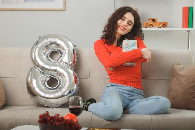 Szczęśliwa i zadowolona młoda kobieta w codziennych ubraniach, uśmiechnięta wesoło, siedząca na kanapie z balonem w kształcie cyfry osiem, obejmująca prezent z okazji międzynarodowego dnia kobiet 8 marca