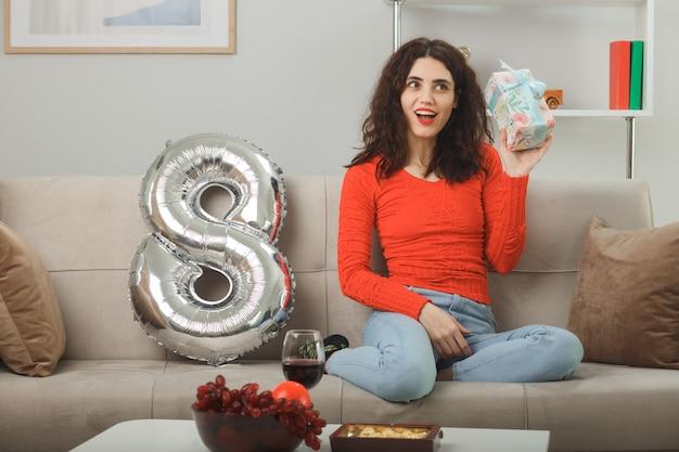 Szczęśliwa i zadowolona młoda kobieta w codziennych ubraniach, uśmiechnięta wesoło, siedząca na kanapie z balonem w kształcie cyfry osiem, trzymająca obecny w jasnym salonie, świętująca międzynarodowy dzień kobiet 8 marca