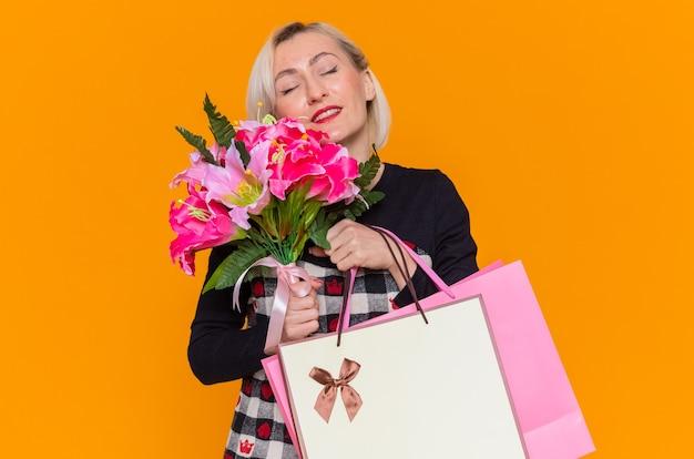Szczęśliwa i zadowolona młoda kobieta w pięknej sukni trzyma bukiet kwiatów i papierowe torby z prezentami, uśmiechając się z okazji międzynarodowego dnia kobiet stojąc nad pomarańczową ścianą