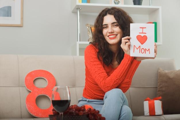 Szczęśliwa i zadowolona młoda kobieta w zwykłych ubraniach siedzi na kanapie z numerem osiem i obecną, trzymając kartkę z życzeniami, uśmiechając się wesoło, świętując międzynarodowy dzień kobiet 8 marca