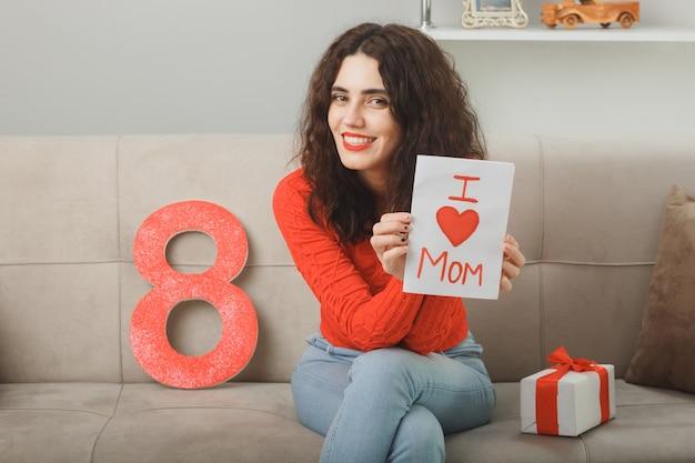 Szczęśliwa i zadowolona młoda kobieta w zwykłych ubraniach siedzi na kanapie z numerem osiem i obecną, trzymając kartkę z życzeniami, uśmiechając się wesoło, świętując międzynarodowy dzień kobiet
