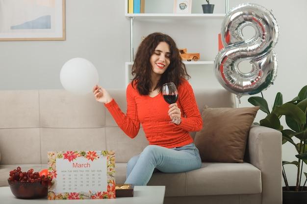 Szczęśliwa i zadowolona młoda kobieta w zwykłych ubraniach uśmiecha się radośnie siedząc na kanapie z kieliszkiem wina trzymając balon w jasnym salonie świętującym międzynarodowy dzień kobiet 8 marca