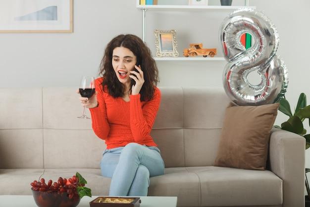 Szczęśliwa i zadowolona młoda kobieta w zwykłych ubraniach uśmiecha się radośnie siedząc na kanapie z lampką wina rozmawiając przez telefon komórkowy w jasnym salonie świętującym międzynarodowy dzień kobiet 8 marca