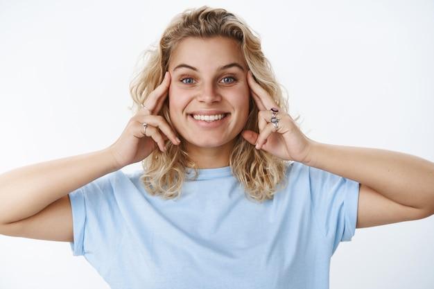 Szczęśliwa i zadowolona urocza europejska blond kobieta o niebieskich oczach trzymająca ręce na twarzy, jakby uśmiechała się w lustrze po nałożeniu kremu lub maseczki na twarz, zadowolona z miękkiej i czystej skóry na białej ścianie