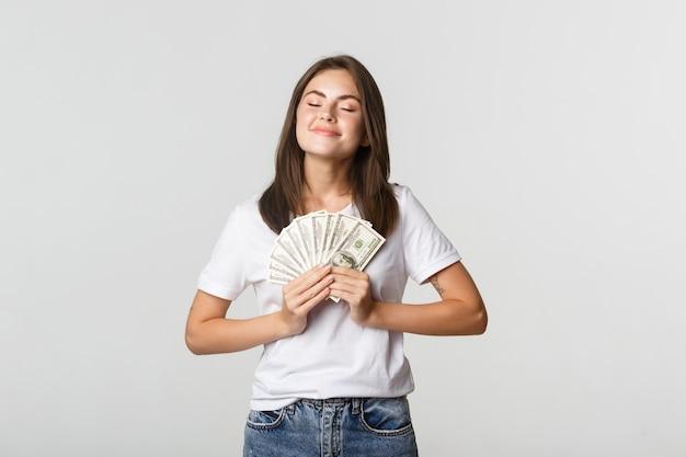Szczęśliwa i zadowolona uśmiechnięta kobieta zamyka oczy i cieszy się posiadaniem pieniędzy.