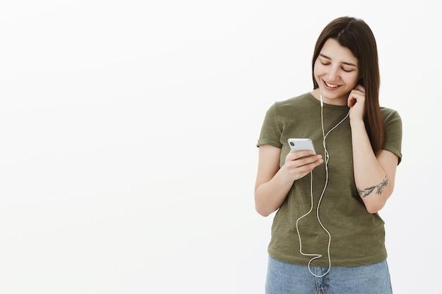Szczęśliwa i zadowolona, wesoła młoda dziewczyna zakłada słuchawki w uchu jako przechyloną głowę i patrzy w dół na ekran smartfona z delikatnym uśmiechem, chcąc posłuchać nowej niesamowitej piosenki, wybierając utwór w aplikacji