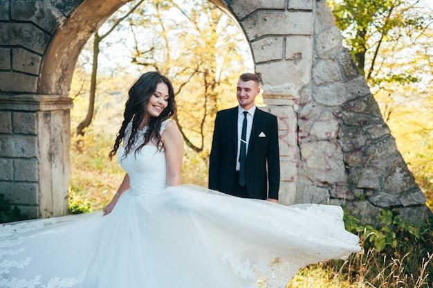 Szczęśliwa i zakochana panna młoda i pan młody spacerują w jesiennym parku w dniu ślubu