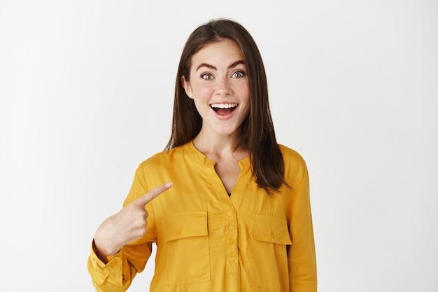 Szczęśliwa i zaskoczona kobieta wskazująca na siebie, patrząca zdumiona w kamerę i uśmiechnięta, wybrana, stojąca nad białą ścianą