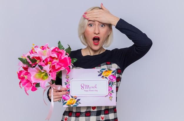 Szczęśliwa i zaskoczona młoda kobieta trzyma kartkę z życzeniami i bukiet kwiatów