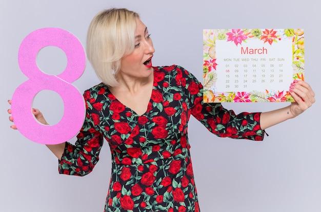 Szczęśliwa i zaskoczona młoda kobieta trzyma papierowy kalendarz miesiąca marca i numer osiem, świętuje międzynarodowy dzień kobiet