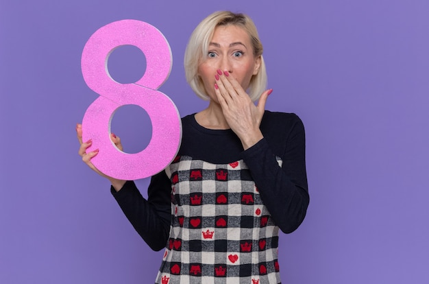 Szczęśliwa i zaskoczona młoda kobieta trzymająca numer osiem