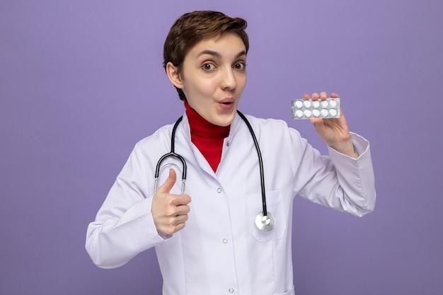 Szczęśliwa i zaskoczona młoda lekarka w białym fartuchu ze stetoskopem na szyi trzymająca blister z tabletkami uśmiechający się radośnie pokazując kciuk do góry stojący na fioletowo