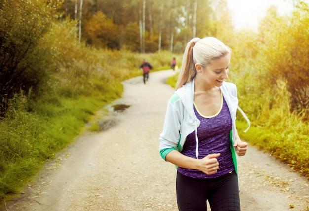 Szczęśliwa i zdrowa dziewczyna biegacz na drodze z innymi biegaczami w oddali