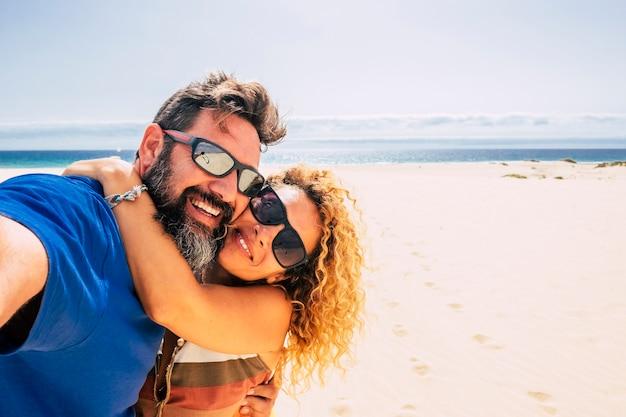 Szczęśliwa i zdrowa para ludzi cieszących się życiem i wakacjami na świeżym powietrzu na plaży