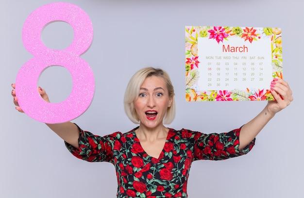 Szczęśliwa i zdziwiona młoda kobieta trzymająca papierowy kalendarz miesiąca marca i numer osiem z kartonu uśmiechnięta wesoło świętująca międzynarodowy marsz z okazji dnia kobiet