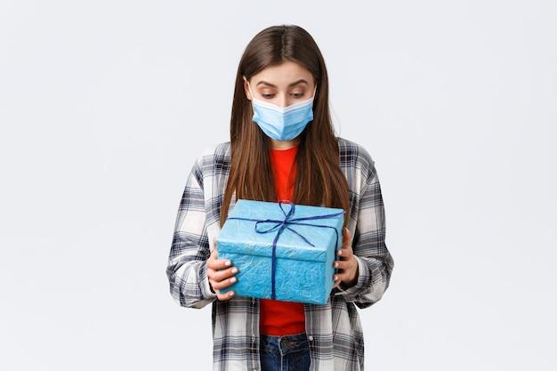 Szczęśliwa i zdziwiona urodzinowa dziewczyna, pracownik otrzymuje prezent od współpracowników, patrząc na zapakowany prezent ze zdumioną wdzięczną twarzą w masce medycznej