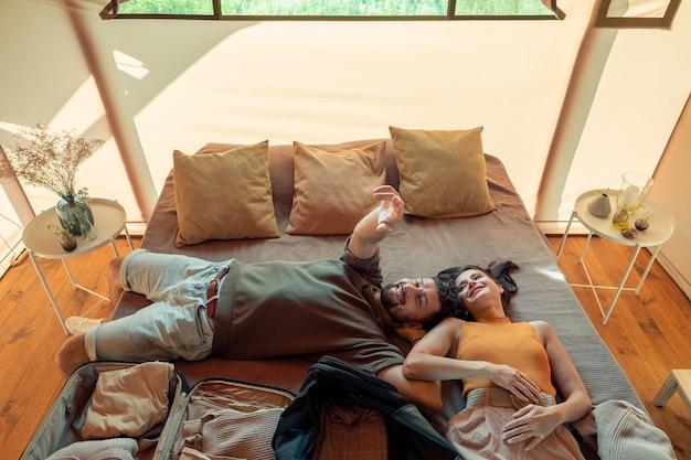 Szczęśliwa idylliczna para relaksuje się na dużym łóżku w domu glampingowym