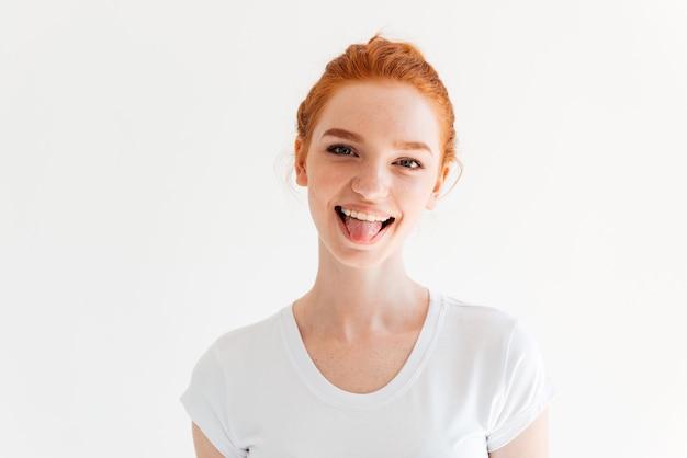 Szczęśliwa imbirowa kobieta w koszulce pokazuje jej język i patrzeje