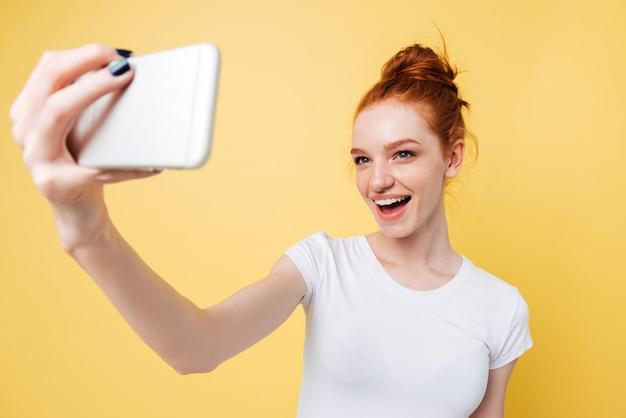 Szczęśliwa imbirowa kobieta w koszulce robi selfie na jej smartphone