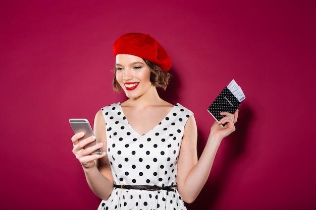 Szczęśliwa imbirowa kobieta w smokingowym mienie paszporcie z biletami i używać smartphone nad menchiami