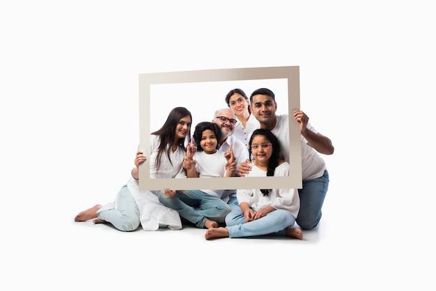 Szczęśliwa indyjska azjatycka wielopokoleniowa rodzina sześciu osób patrząca przez pustą ramkę, stojąca lub siedząca na białym tle, ubrana w białe ubrania i niebieskie dżinsy