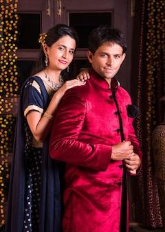 Szczęśliwa indyjska młoda para w namaskara lub ręce złożone poza na festiwalu diwali, witając gości
