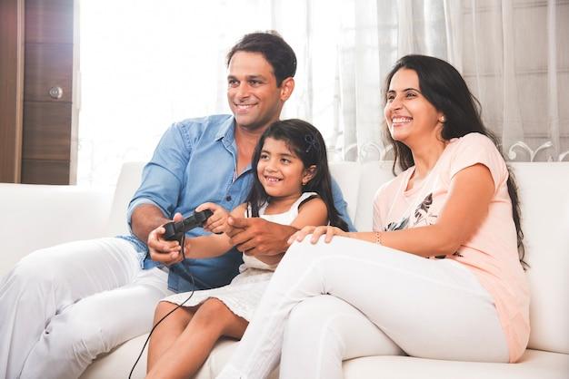 Szczęśliwa indyjska rodzina azjatów grająca w domu w grę wideo za pomocą joysticka lub kontrolera