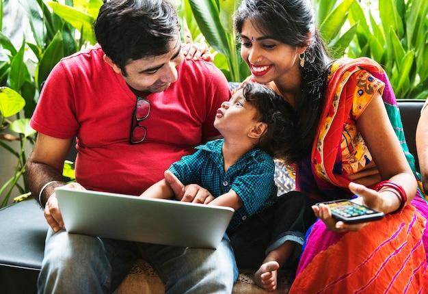 Szczęśliwa indyjska rodzina korzystająca z laptopa