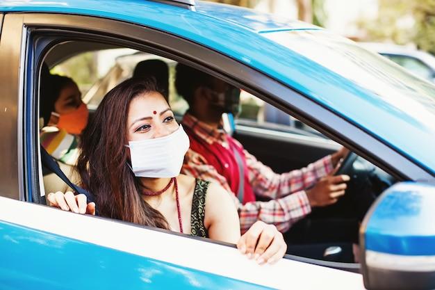 Szczęśliwa indyjska rodzina nosząca maseczki ochronne na twarz przed koronawirusem podróżująca razem samochodem car