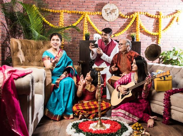 Szczęśliwa indyjska rodzina śpiewa, gra na gitarze, świętuje festiwale w tradycyjnych strojach