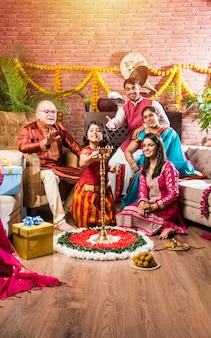 Szczęśliwa indyjska rodzina świętująca ganesh festival lub chaturthi powitanie lub wykonanie pooja i jedzenie słodyczy w tradycyjnym stroju w domu ozdobionym kwiatami nagietka
